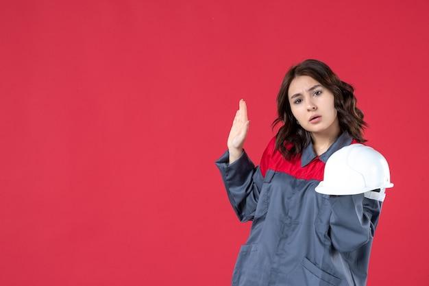 Vista frontale dell'architetto femminile confuso che tiene il cappello duro e che solleva la mano sulla parete rossa isolata