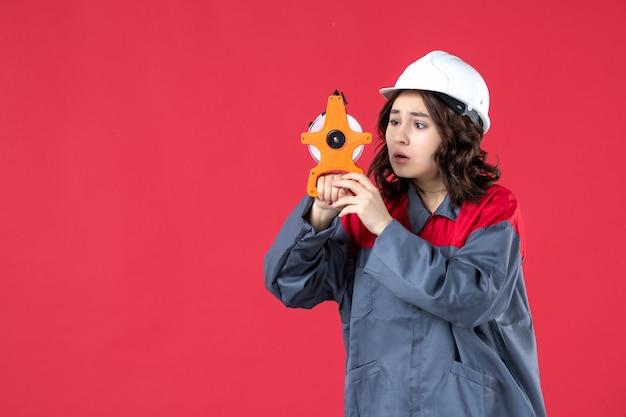 Vista frontale dell'architetto femminile confuso in uniforme con il nastro di misurazione della tenuta del cappello duro e messo a fuoco su esso sulla parete rossa isolata