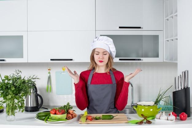 Вид спереди сбит с толку повар-женщина в фартуке, глядя на продукты на столе