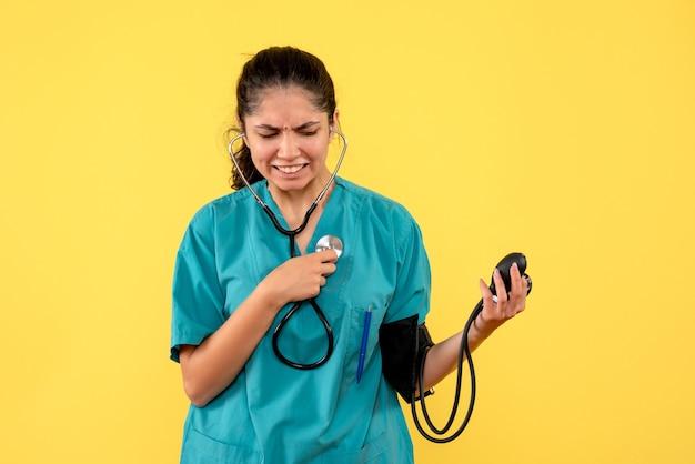 Medico femminile confuso vista frontale in uniforme che tiene sfigmomanometri in piedi su sfondo giallo