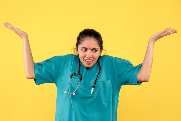 Вид спереди сбит с толку женщина-врач со стетоскопом, открывающая руки, стоя на желтом фоне