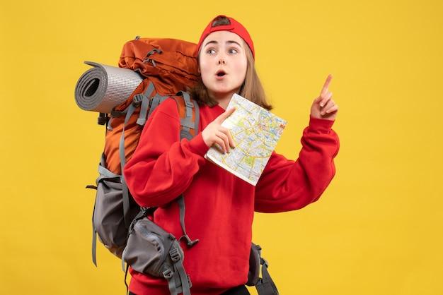 Вид спереди сбит с толку туристка с красным рюкзаком, держащим карту