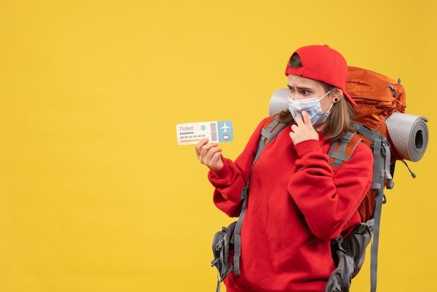 Viaggiatore femminile confuso vista frontale con zaino e maschera che tiene biglietto aereo