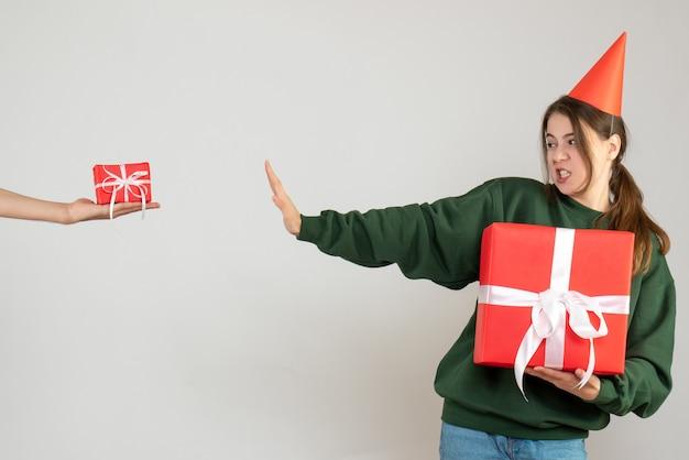 Vista frontale ragazza confusa con tappo del partito che tiene il suo regalo di natale mano umana che tiene il regalo