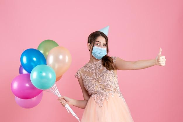 Ragazza confusa di vista frontale con il cappuccio del partito e la mascherina medica che fa pollice sul segno che tiene i palloncini colorati