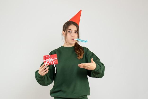 Vista frontale ragazza confusa con il tappo del partito che punta al suo regalo di natale utilizzando noisemaker