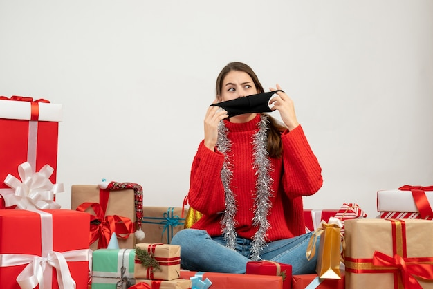 Front view confused girl with red sweater taking off her mask sitting around presents
