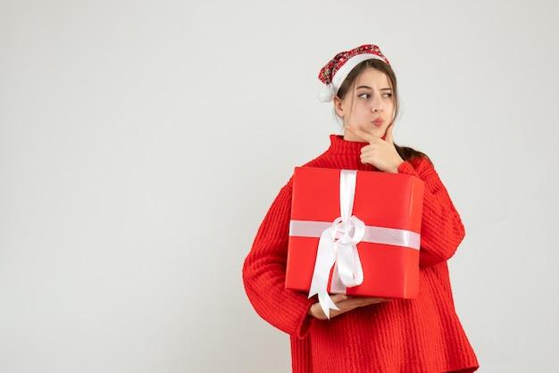 전면보기는 그녀의 크리스마스 선물을 들고 산타 모자와 소녀를 혼란