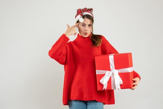 현재 퍼팅 손가락 총을 들고 산타 모자와 전면보기 혼란 소녀