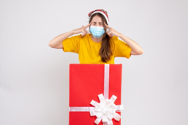 큰 크리스마스 선물 뒤에 서있는 산타 모자와 전면보기 혼란 된 소녀