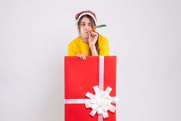 Front view confused girl with santa hat using noisemaker standing behind big xmas gift