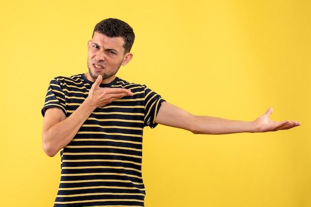 正面図は、黒と白の縞模様のtシャツ黄色の孤立した背景のハンサムな男性を混乱させた