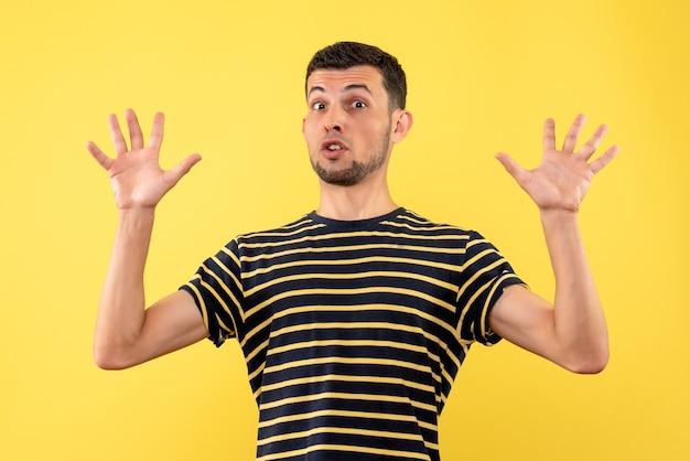 Vista frontale uomo bello confuso in maglietta a righe bianco e nero che solleva le mani su sfondo giallo isolato