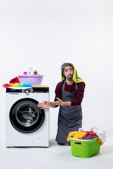 Front view confused housekeeper man standing on knee near washing machine on white background
