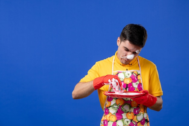Front view confused housekeeper with foam on his face washing plate on blue space