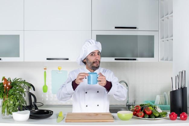 부엌 테이블 뒤에 서 있는 파란색 컵을 들고 요리사 모자를 쓴 남성 요리사의 전면 보기
