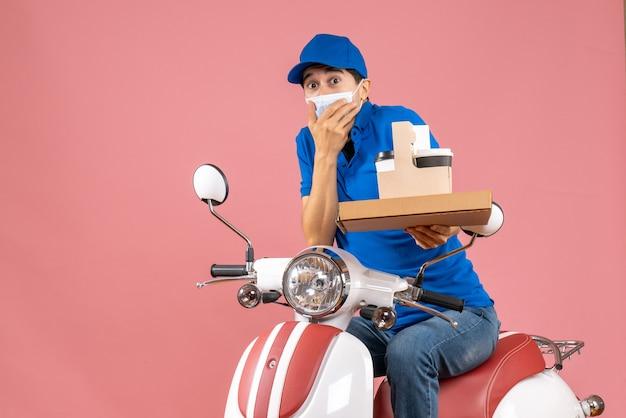 Vista frontale del fattorino maschio confuso in maschera con cappello seduto su uno scooter che mostra ordini su sfondo pesca pastello pastel