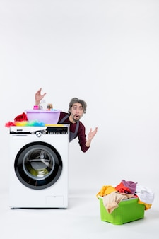 Front view confused male housekeeper in apron sitting behind washer laundry basket on white isolated background