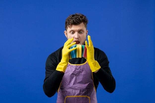 Front view confused male housekeeper holding dish sponges on blue space