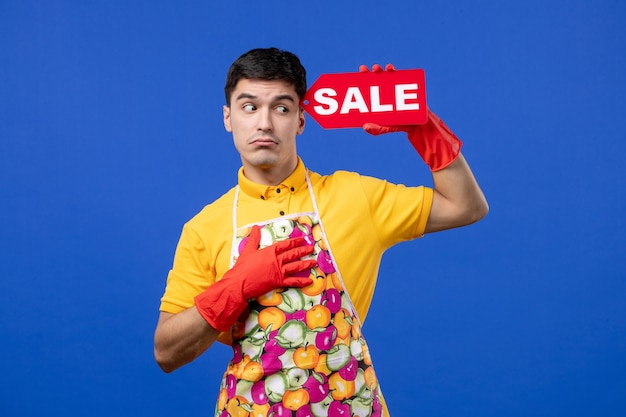 파란색 공간에 판매 표시를 들고 노란색 티셔츠에 남성 가정부를 혼란스럽게 전면보기