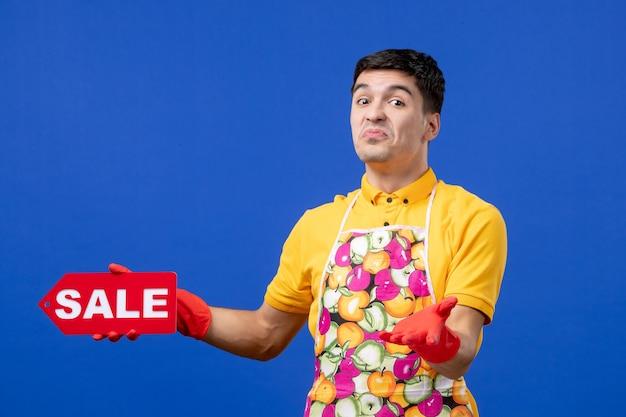 Vista frontale confusa governante maschio in maglietta gialla con cartello di vendita su spazio blu