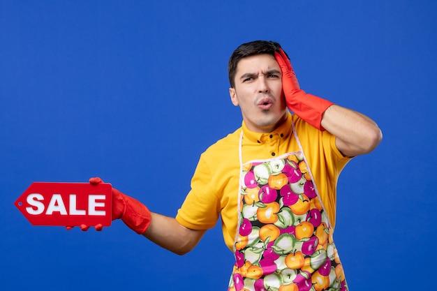 Vista frontale confusa governante maschio in maglietta gialla con cartello di vendita che tiene la testa su uno spazio blu