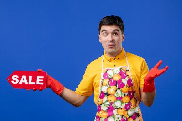 Vista frontale confusa governante maschio in maglietta gialla con cartello di vendita che apre le mani sullo spazio blu