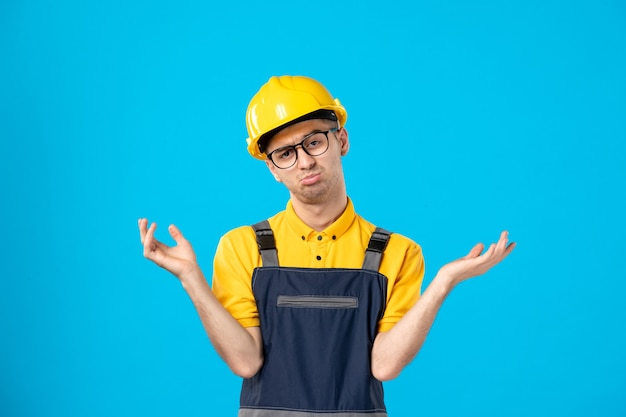 Front view confused male worker in yellow uniform on blue