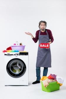 Vista frontale uomo confuso in grembiule che regge il cartello di vendita in piedi vicino al cesto della biancheria della lavatrice su sfondo bianco
