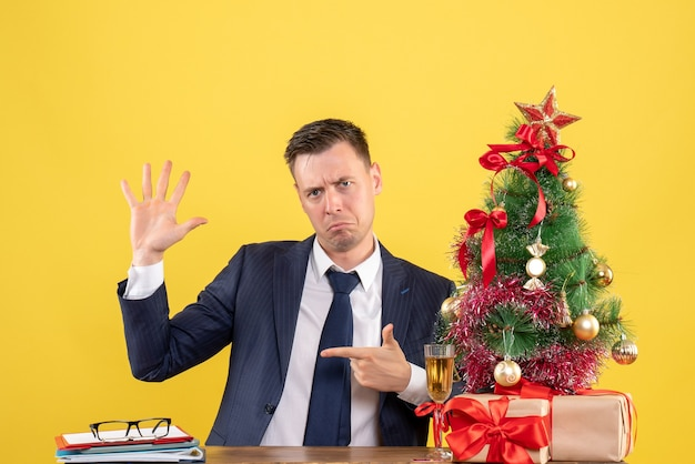 Front view of confused man opening his hand sitting at the table near xmas tree and presents on yellow