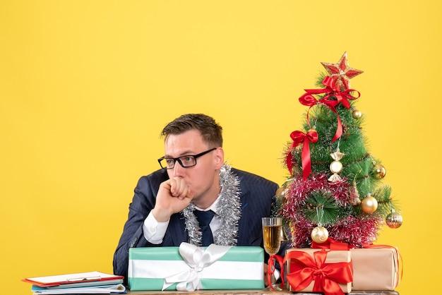 Vista frontale dell'uomo confuso seduto al tavolo vicino all'albero di natale e regali su giallo