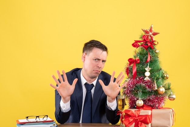 Front view of confused man with opened hands sitting at the table near xmas tree and presents on yellow