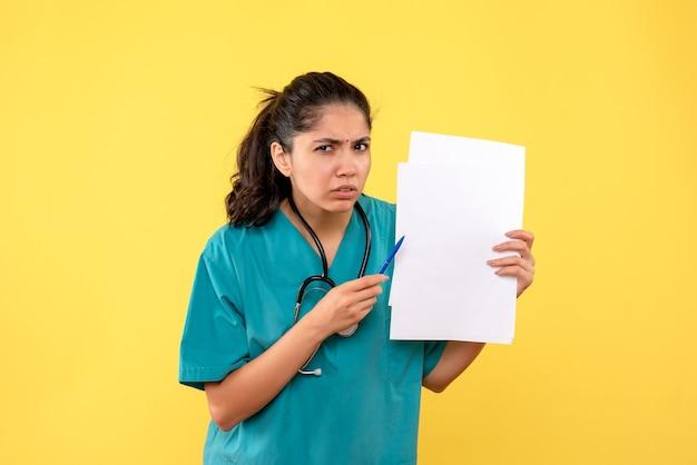 Medico femminile abbastanza confuso vista frontale che tiene documenti e penna su sfondo giallo