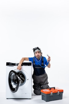 Front view confused repairman with stethoscope sitting near washer on white space