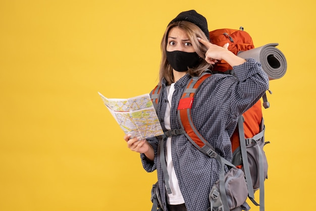 Vista frontale della ragazza del viaggiatore confuso con maschera nera e mappa della holding dello zaino