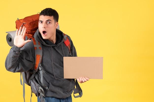Vista frontale uomo viaggiatore confuso con zaino che tiene cartone agitando la mano