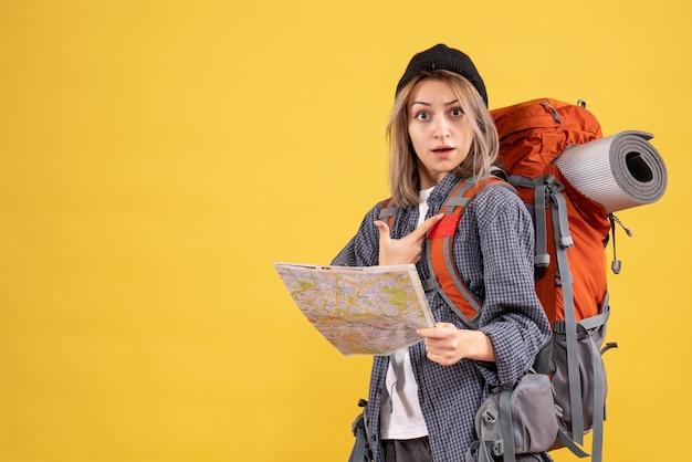Vista frontale della donna del viaggiatore confuso con lo zaino che tiene la mappa che punta a se stessa