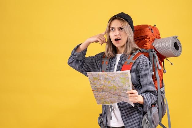 Vista frontale del viaggiatore confuso donna con zaino alzando la mappa