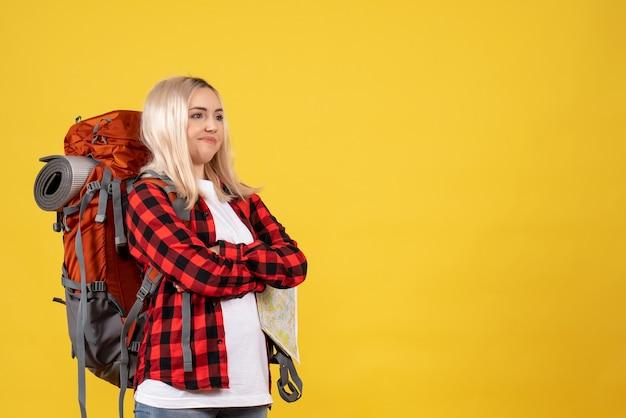 黄色の壁に立っている彼女のバックパックの交差する手で正面図混乱した旅行者の女性
