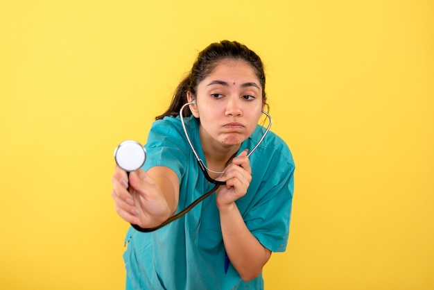 Medico donna confuso vista frontale in uniforme utilizzando uno stetoscopio su sfondo giallo