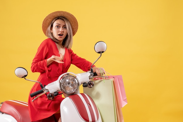Front view of confused woman in red dress on moped holding shopping bags