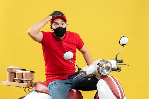 Vista frontale del giovane adulto confuso che porta i guanti rossi della camicetta e del cappello nella mascherina medica che trasporta l'ordine che si siede sul motorino su fondo giallo