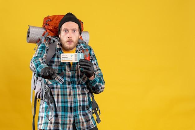 Vista frontale del giovane viaggiatore con zaino e sacco a pelo confuso con il biglietto aereo della tenuta del cappello nero che indica qualcosa