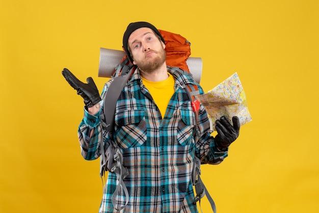 Vista frontale del giovane viaggiatore con zaino e sacco a pelo confuso con la mappa di viaggio della holding del cappello nero