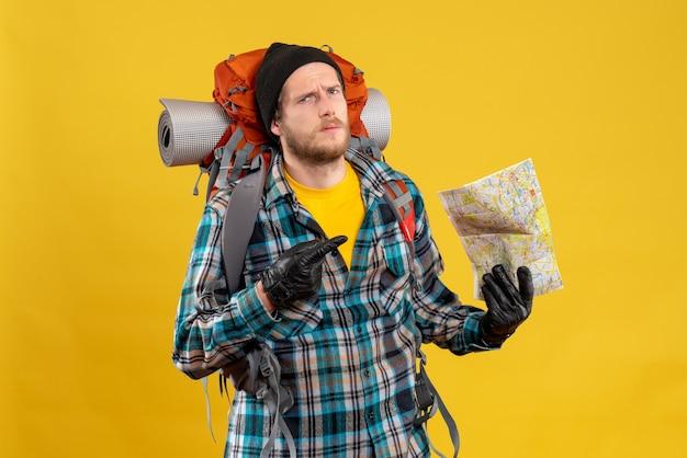 Vista frontale del giovane viaggiatore con zaino e sacco a pelo confuso con il cappello nero che indica alla mappa