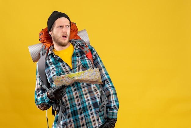 Vista frontale del giovane viaggiatore con zaino e sacco a pelo confuso con i guanti di cuoio che tengono la mappa di viaggio