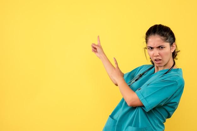 Vista frontale confuso giovane medico femminile che punta con il dito dietro su sfondo giallo