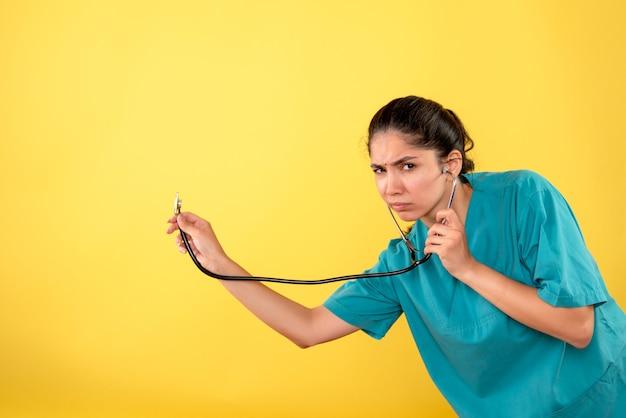 Vista frontale confuso giovane medico femminile con lo stetoscopio su sfondo giallo
