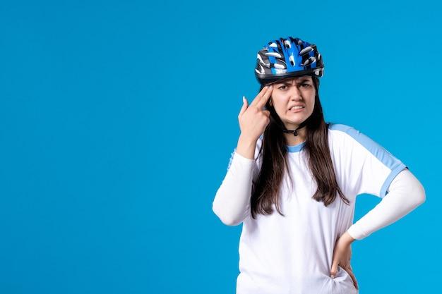 正面図ヘルメットとスポーツ服を着た若い女性を混乱させる