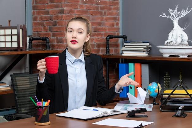 Vista frontale di una giovane donna confusa seduta a un tavolo e con in mano una tazza rossa in ufficio